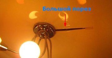 Большой на натяжном потолке порез рядом с люстрой