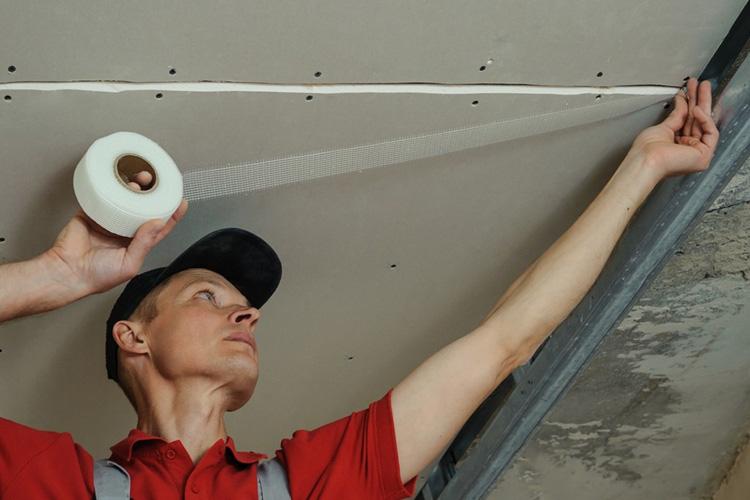 При отделке потолка из гипсокартона стыки между листами можно заклеить лентой или специальным скотчем