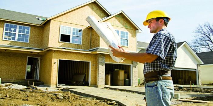 Рабочий изучает проект перед домом